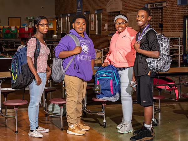 Teens holding backpacks