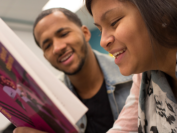 Girl reading book with mentor