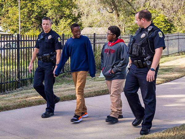 Boys walking casually alongside police officers